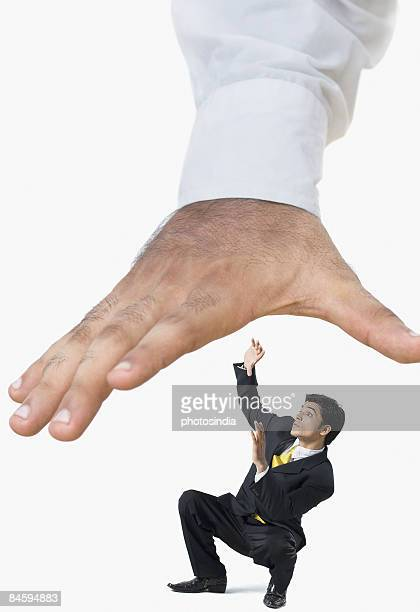 Businessman being crushed under a human hand