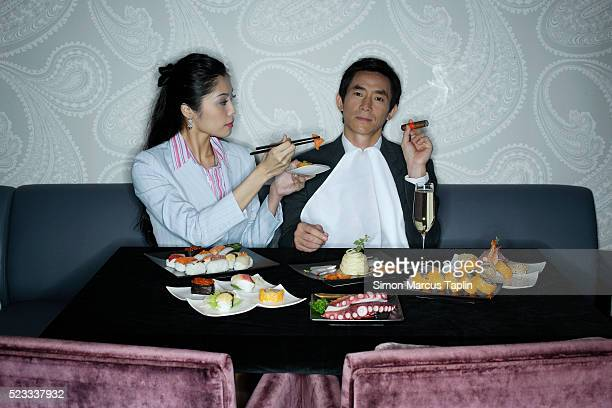 Businessman Being Feed Sushi Dinner