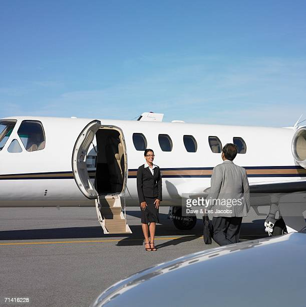 Businessman being greeted by flight attendant at airplane