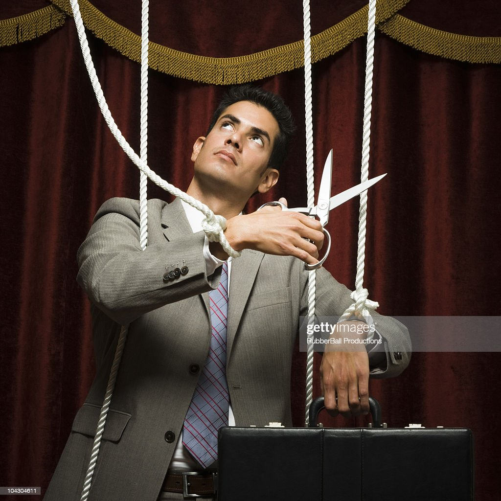 businessman being pulled by strings like a puppet : Stock Photo