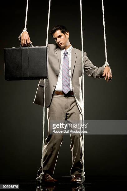 businessman being pulled by strings like a puppet