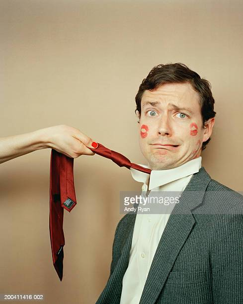 Businessman being pulled by tie with kisses on his face, portrait