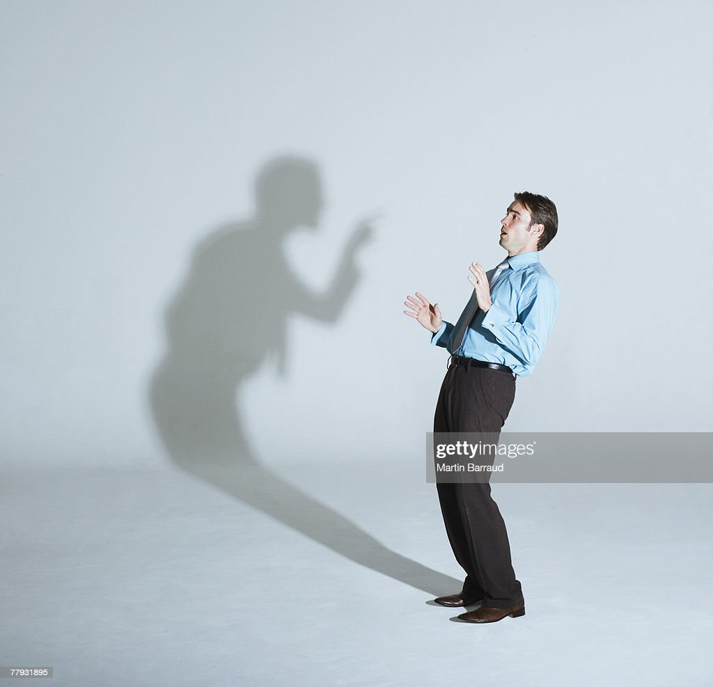 Businessman being scolded by his shadow : Stock Photo