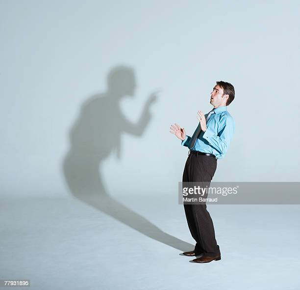 businessman being scolded by his shadow - toned image stock pictures, royalty-free photos & images