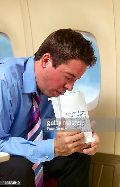 businessman being sick on plane - sick bag stock photos and pictures