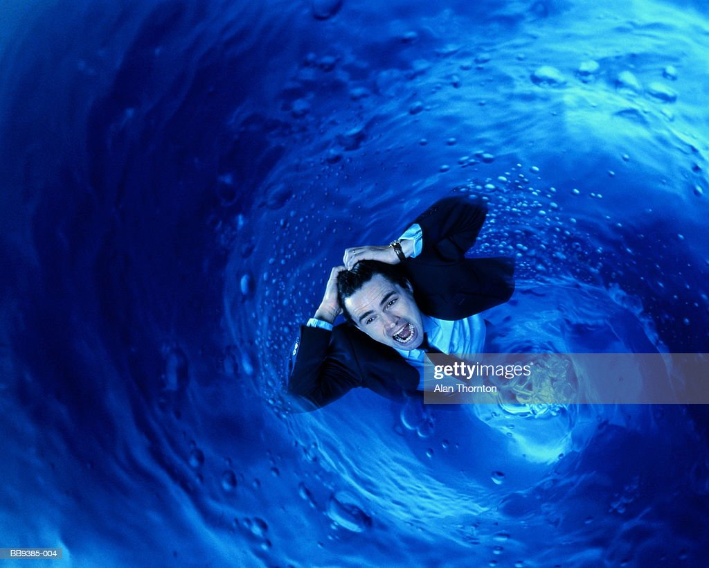 Businessman being sucked into whirlpool (Digital Composite) : Stock Photo