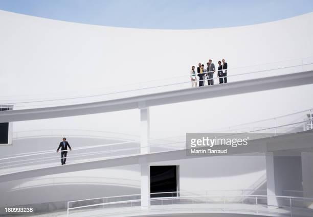 Businessman below business people on elevated walkway