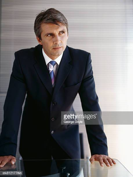 businessman bending over a table and looking sideways