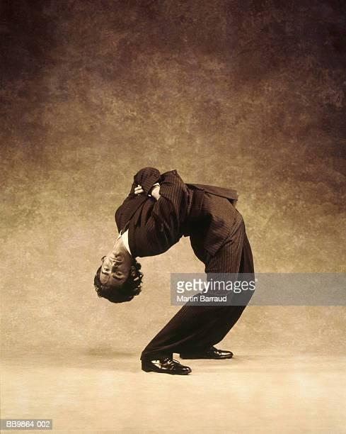 businessman bending over backwards (toned b&w) - inarcare la schiena foto e immagini stock