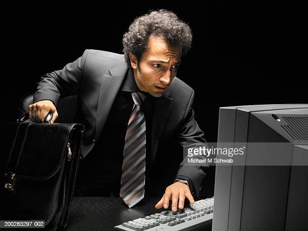 businessman bending over desk, looking at computer screen, frowning - michael turk stock pictures, royalty-free photos & images