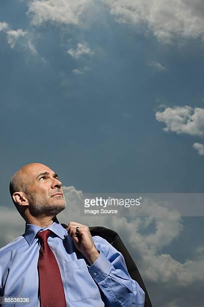 Businessman beneath a cloudy sky