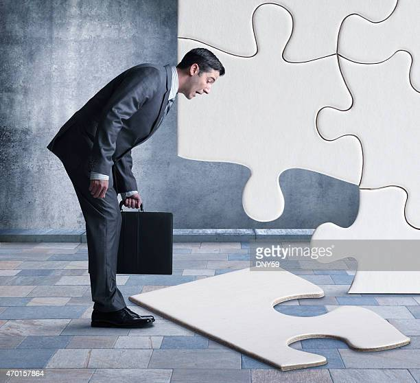 businessman bent over looking at missing piece of puzzle - bending over stock pictures, royalty-free photos & images