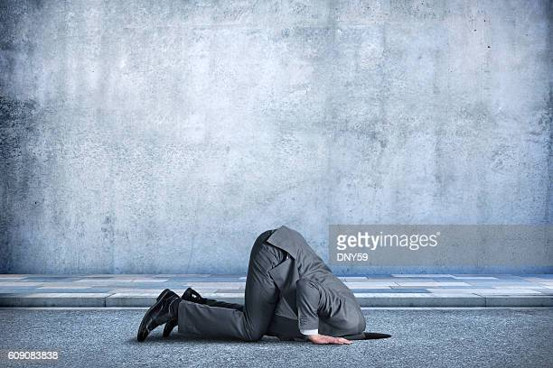 Businessman Bent Over With His Head In A Hole