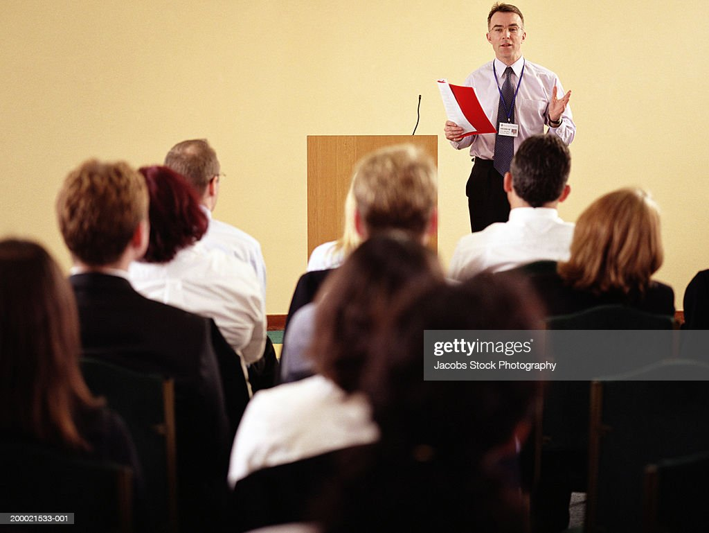 Businessman beside podium addressing colleagues : Stock Photo