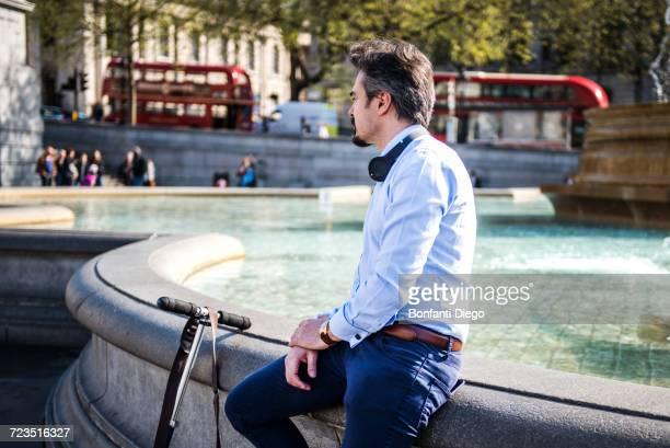 Businessman beside scooter, Trafalgar Square, London, UK