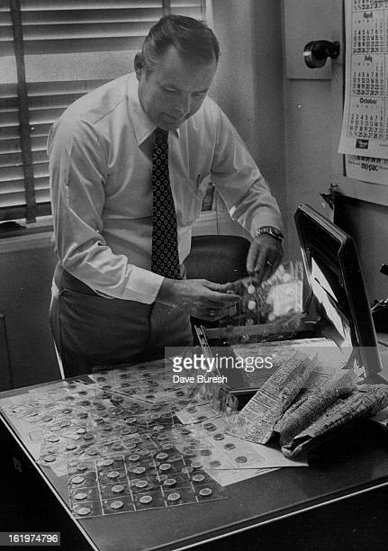 OCT 18 1977 Businessman Bilked With Fake Russian Coins Detective Ed Hesse of the Denver Police Department looks at worthless coins used to bilk a...