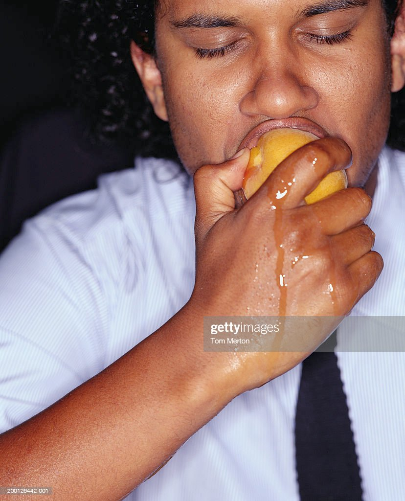 Businessman biting peach, juice running down hand, close-up : Stock Photo