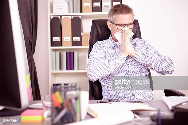 Businessman blowing nose at home office
