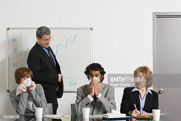 Businessman blowing nose in office