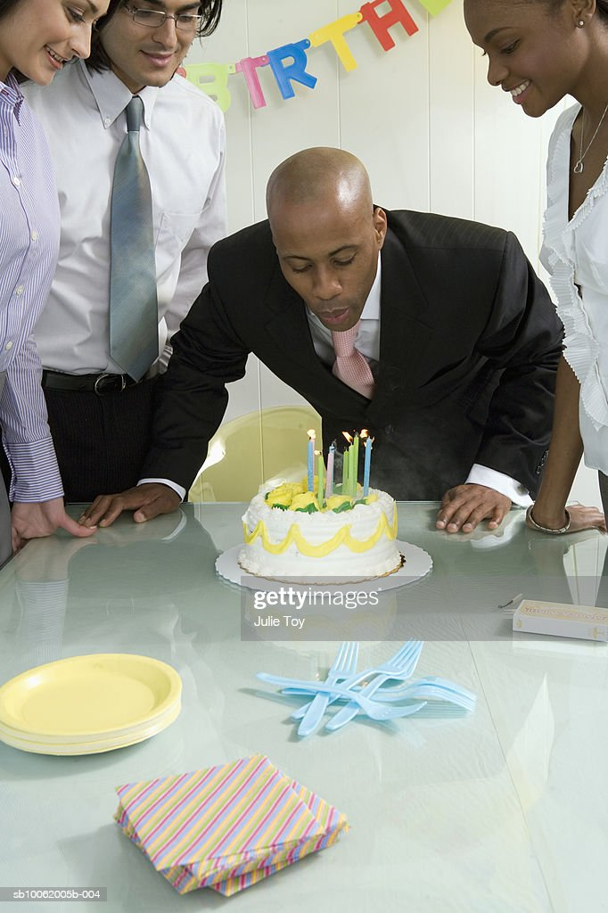 Businessman Blowing Out Candles On Cake Stock Photo