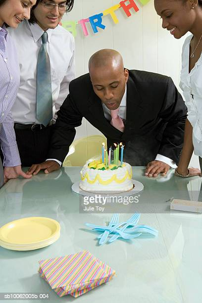 Businessman Blowing Out Candles on Cake