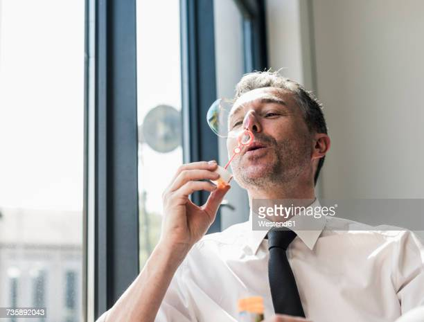 Businessman blowing soap bubbles