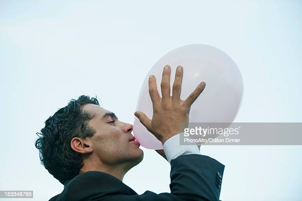 Businessman blowing up balloon, side view