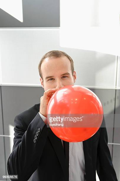 Businessman blowing up red balloon