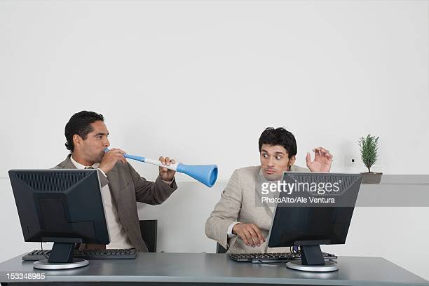 Businessman blowing vuvuzela horn into colleague's ear