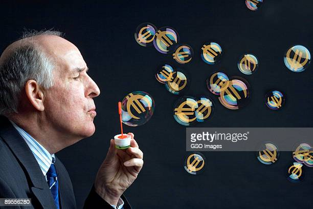 Businessman blows bubbles with Euro