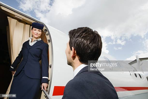 Businessman boarding corporate airplane