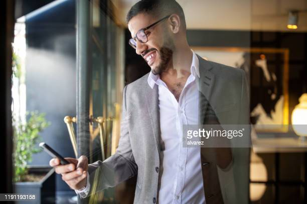 businessman booking an online taxi from his phone - guest stock pictures, royalty-free photos & images