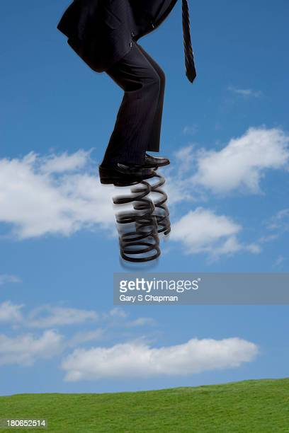 Businessman bouncing on large springs