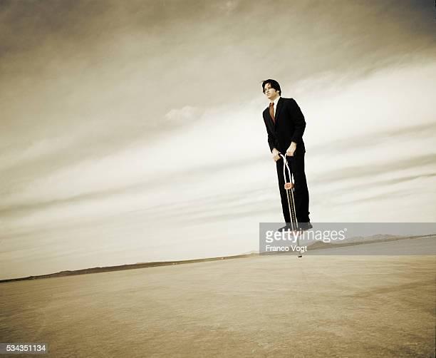 Businessman Bouncing on Pogo Stick in Desert