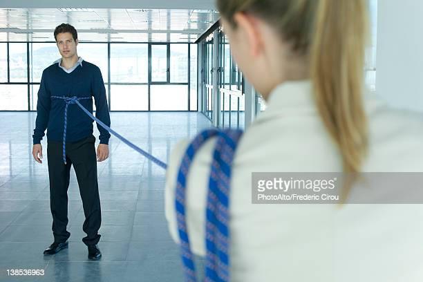 Businessman bound in rope