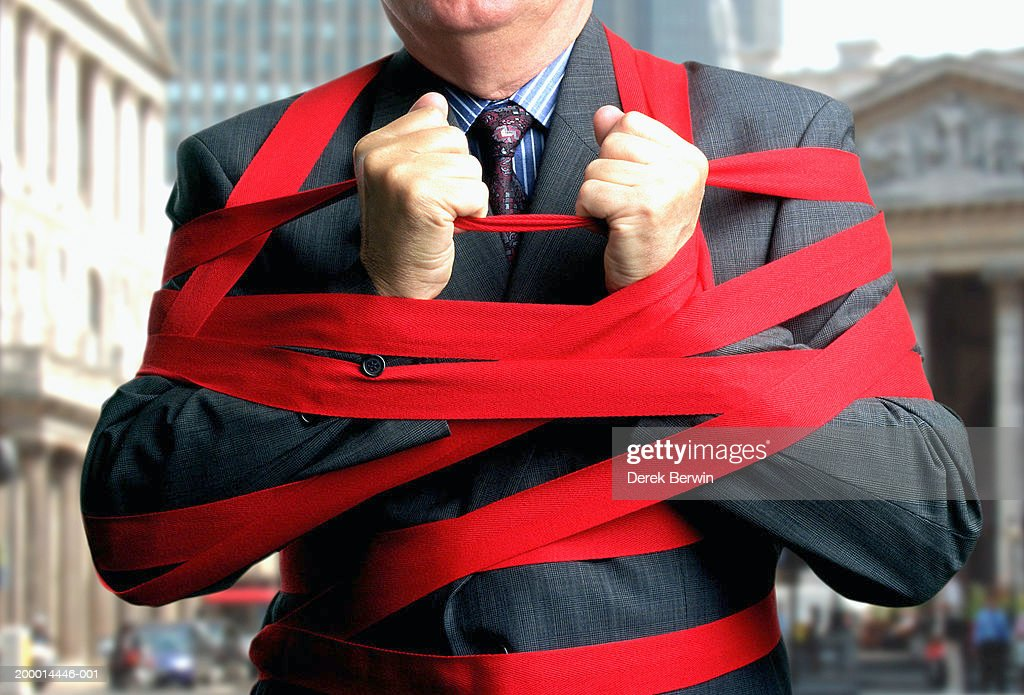 Businessman bound up in red tape, mid section, close-up : Stock Photo