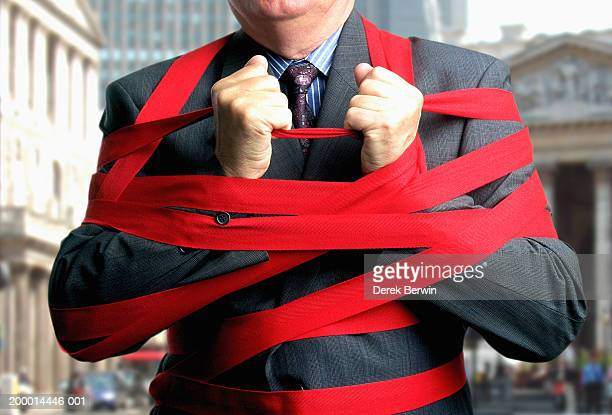 Businessman bound up in red tape, mid section, close-up