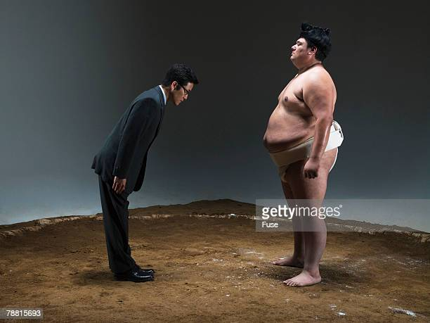 Businessman Bowing to Sumo Wrestler