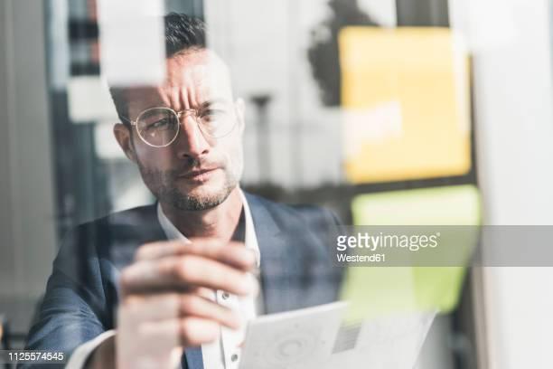 businessman brainstorming in office, using sticky notes - koordination stock-fotos und bilder