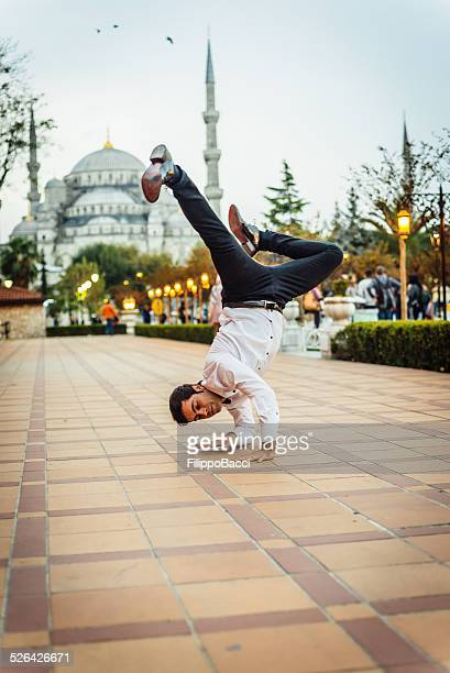 businessman breakdancing in front of blue mosque - soul train dancers stock photos and pictures