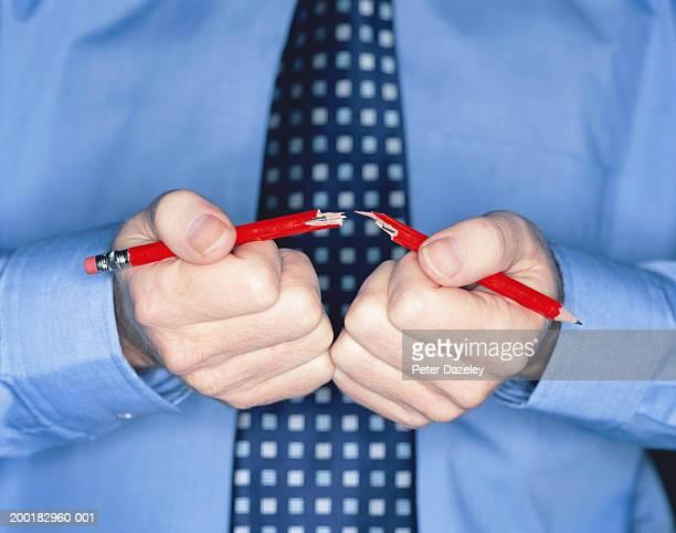 Businessman breaking pencil, close-up