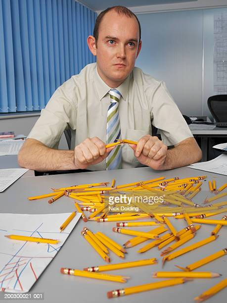 Businessman breaking pencil in half by pile of pencils on desk