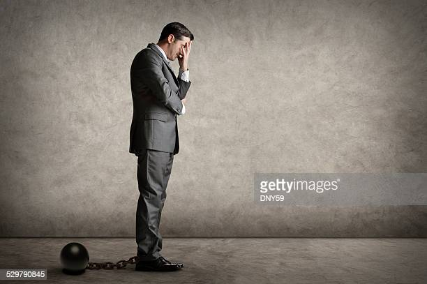 Businessman Burdened By A Ball And Chain