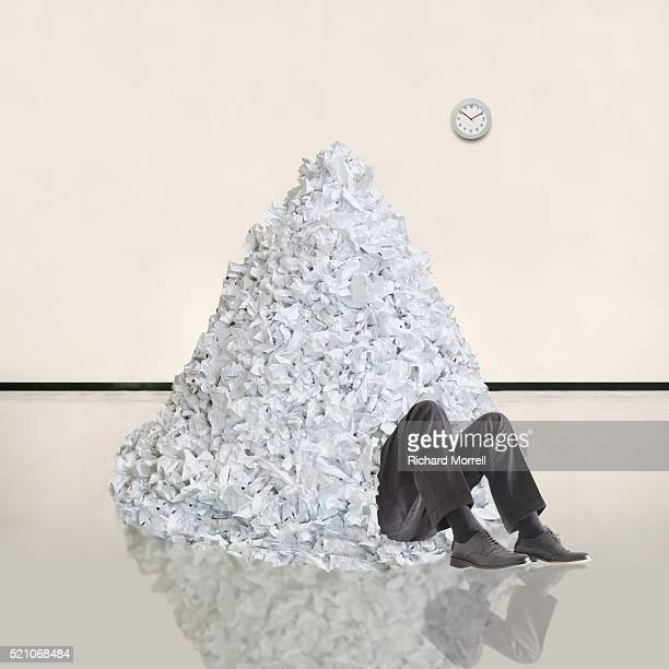 Businessman Buried Beneath Pile of Paper