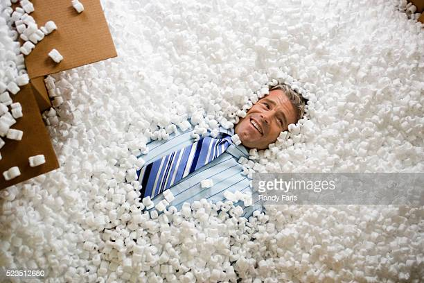 Businessman Buried by Packing Peanuts