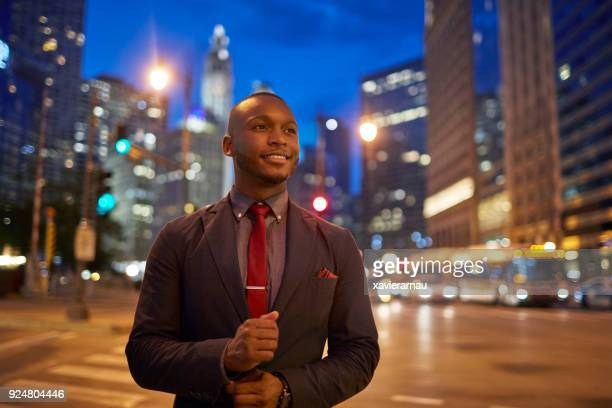 businessman buttoning cuff in illuminated city - cuff sleeve stock pictures, royalty-free photos & images