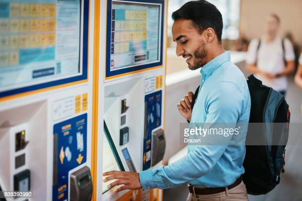 Businessman buying railway ticket on machine and using contactless payment method