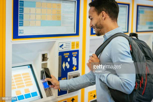 Businessman buying train ticket on ticket machine and paying by phone