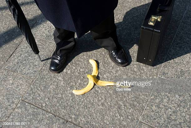 Businessman by discarded banana skin, low section, elevated view