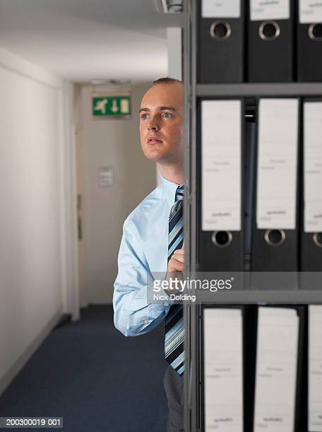 Businessman by shelves of files
